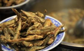 河南有种传统美食用小鱼做成,先炸后炖,锅底扣个瓷碗是制作关键